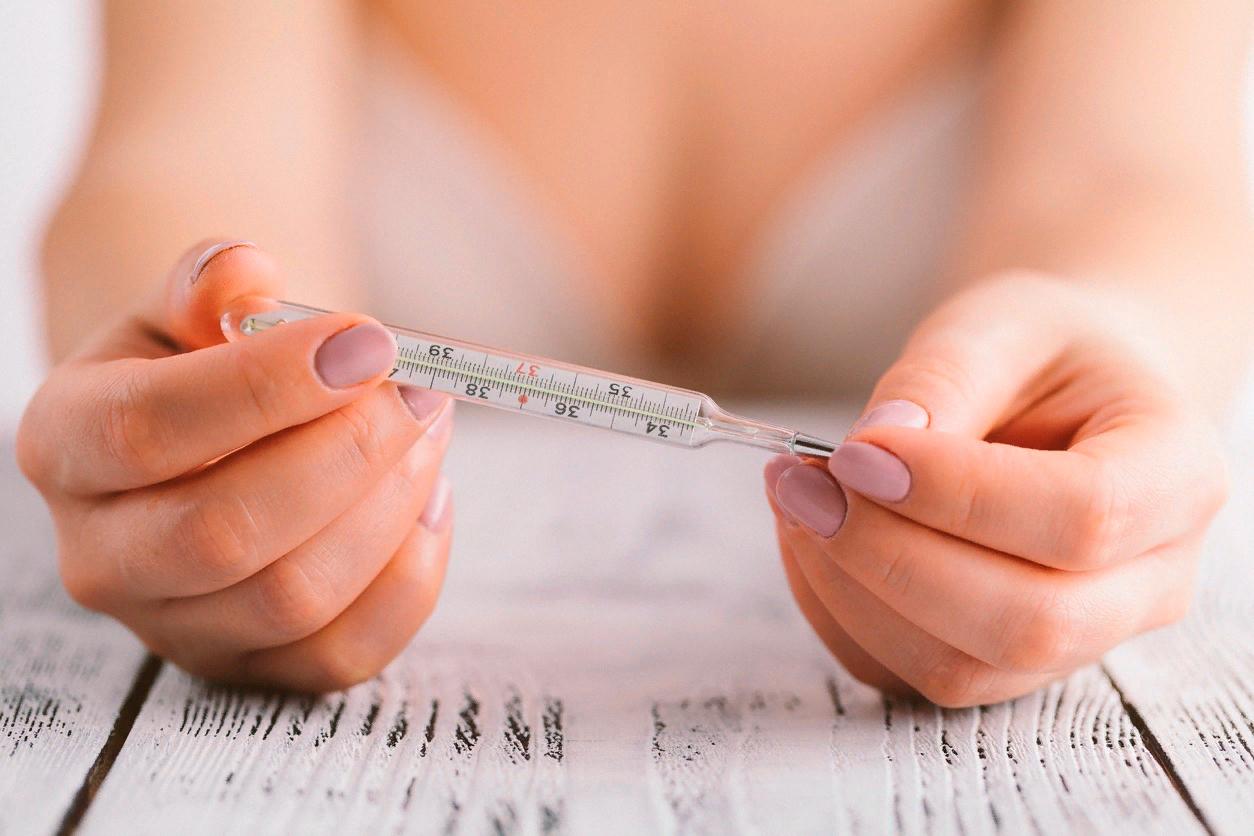 Девушка держит термометр