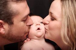 Родители целуют малыша