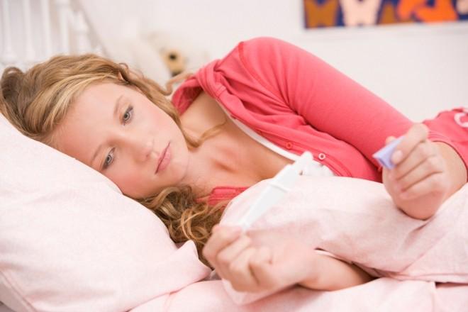 Девушка держит тест на беременность